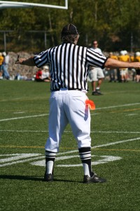 Football referee with arms outreasched to both sides which symbolizes what churches should think about when choosing church membership software and why one is better over the other for that church