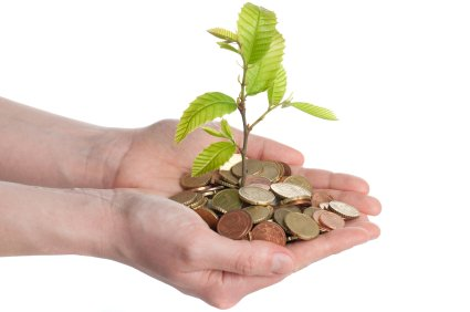 money coins in human hands with a tree sapling growing out of it denoting free church accounting software