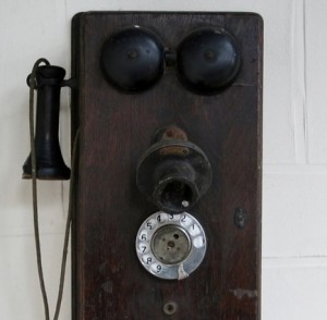 Antique brown phone hanging on the wall.