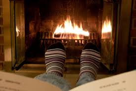 Person reading cozy up next to a fire