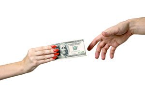 A man's hand handing one hundred dollar bills to a woman's hand.