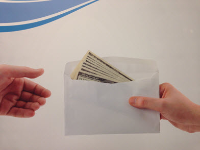 Envelope of 100 dollar bills being handed from one person to another.