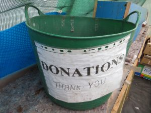bucket with a sign on it saying donations and thank you. symbolizes taking donations in for flood relief