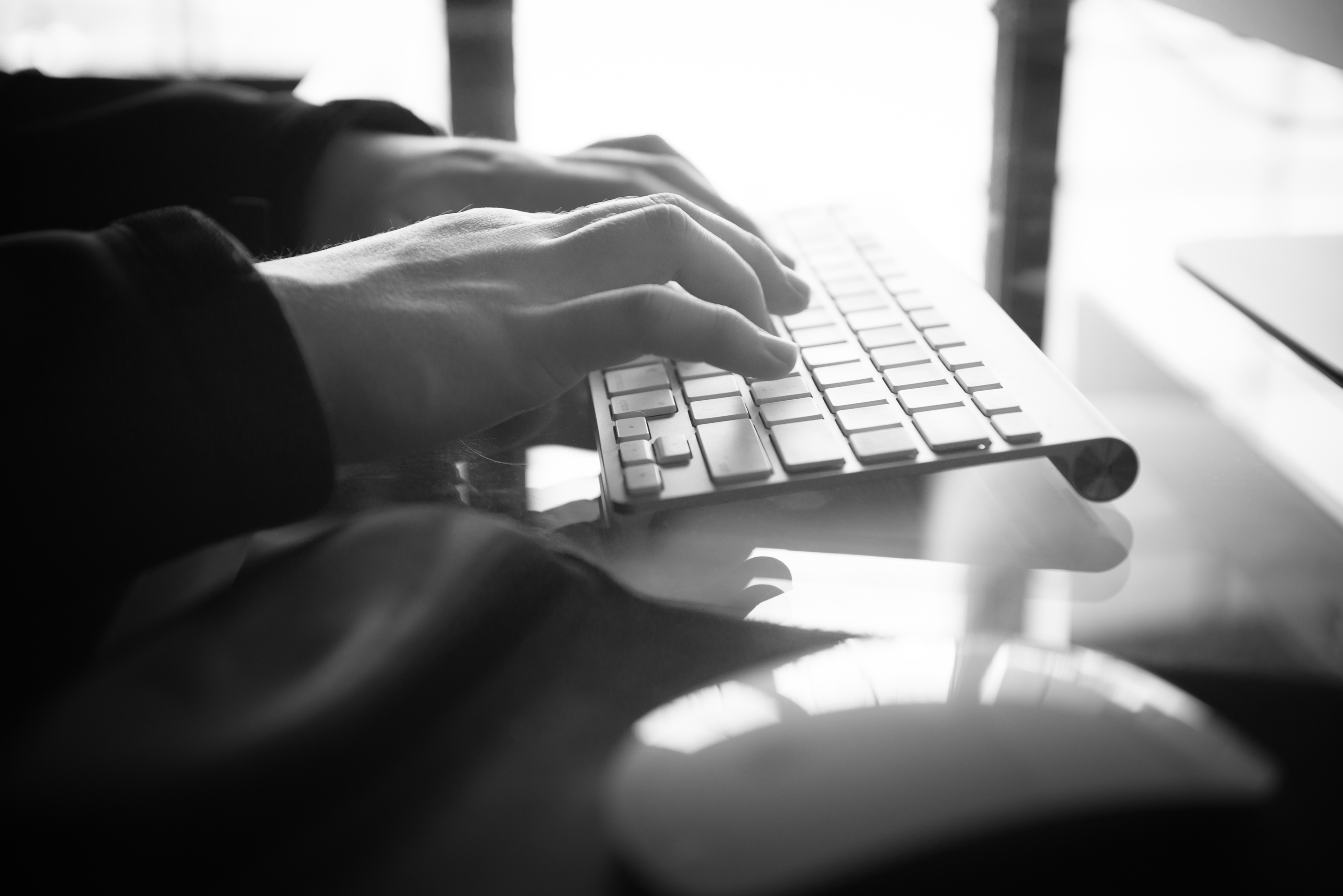 photos of hands typing at a keyboard on a desk