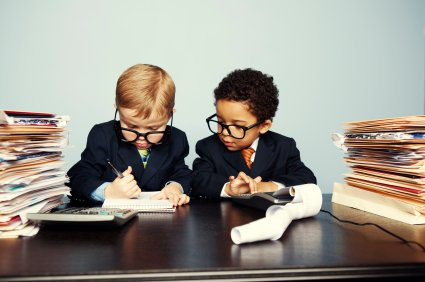 Two kids in suits with stacks of accounting records and a calculator in front of them working on taxes for churches