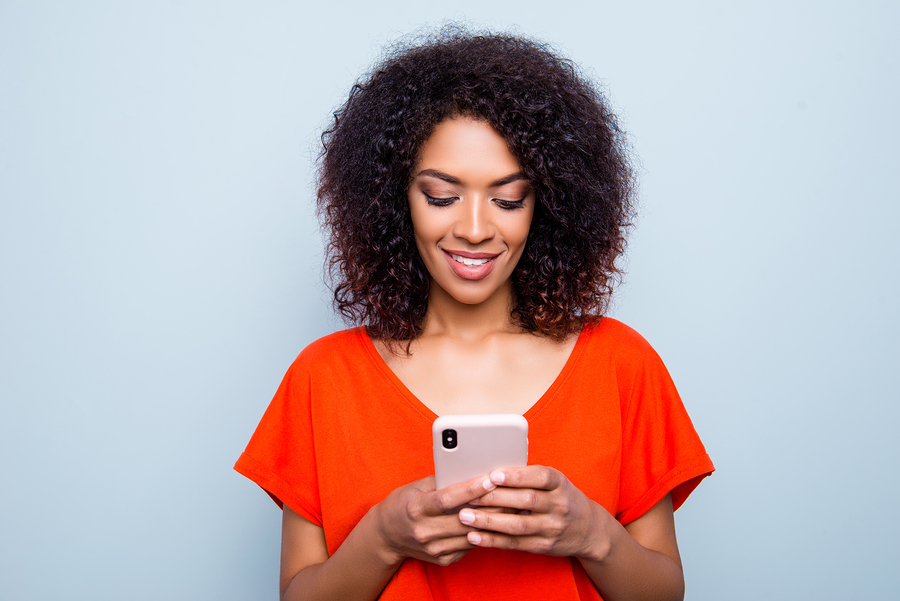 Portrait of busy charming woman with modern hairdo in vivid outfit holding smart phone in hands using wi-fi 3G internet checking email searching contact isolated on grey background