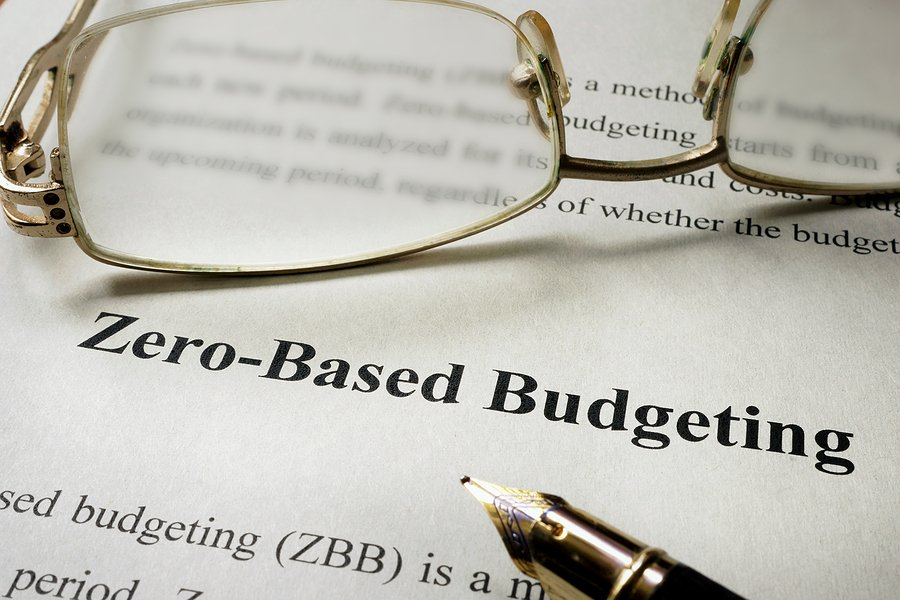 Shows a person's glasses and pen with the words zero based budgeting on the paper underneath