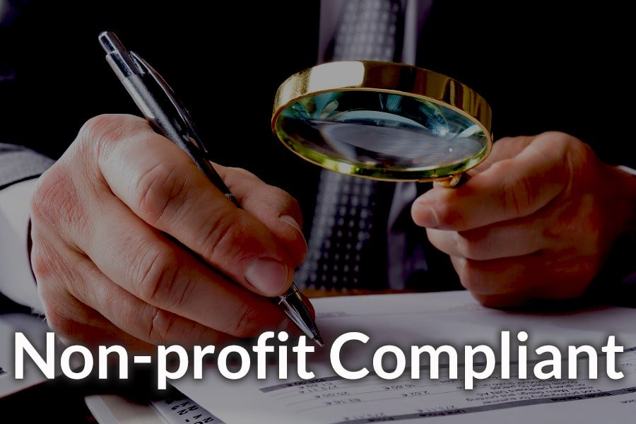 A man holding a magnifying glass illustrating accounting compliance.