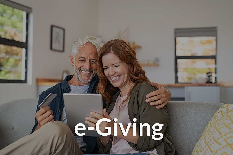 A couple giving to their church through a mobile device and the church's e-Giving platform.