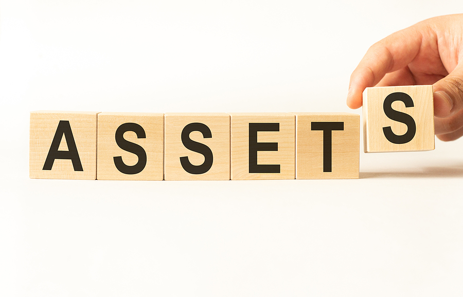 Wooden blocks with the word assets and a hand putting on the last letter 's' on the end.