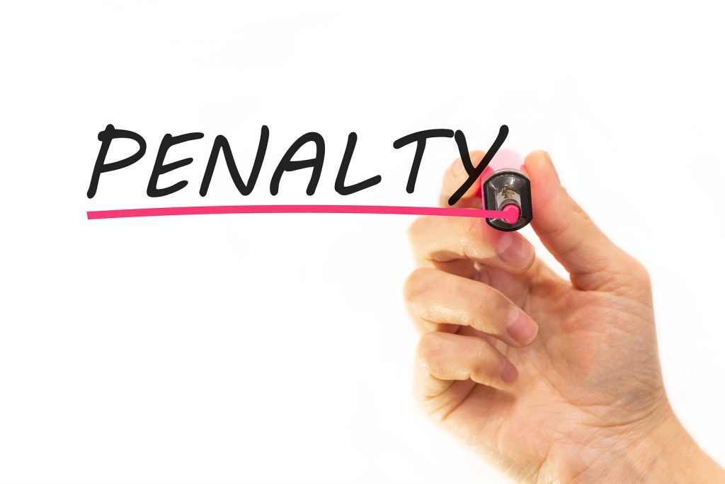 A hand writing the word penalty in black text with red underline.